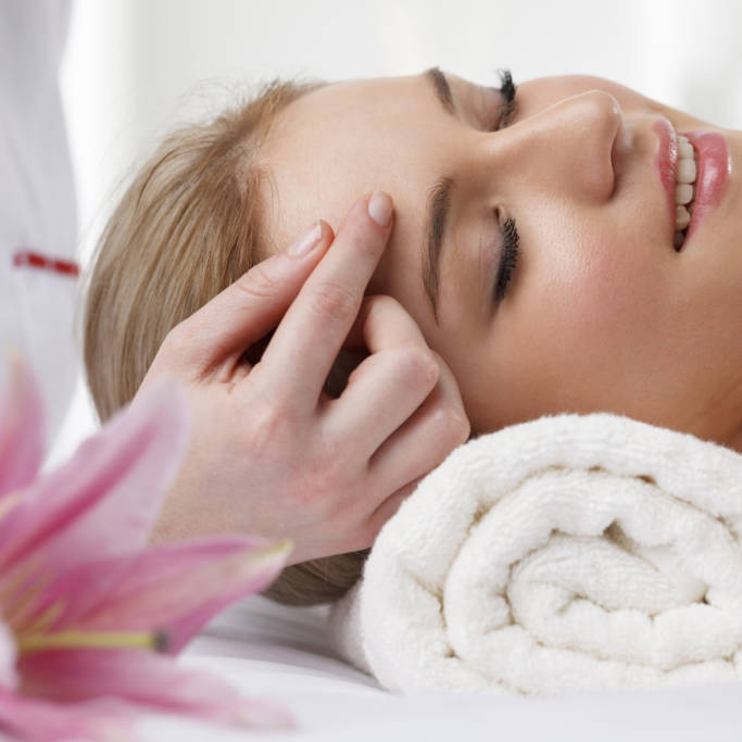 Close-up of a beautiful woman receiving head massage at spa.