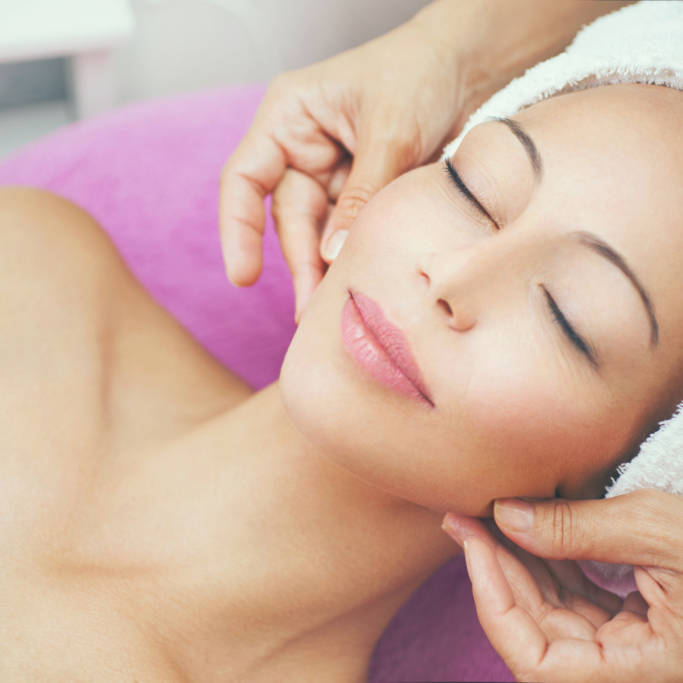 Closeup of adult caucasian woman having her face pampered at beauty salon by mid aged professional female beautician. The client is relaxing on massage bed wrapped in white towel. Top view shot. Tilt shot.